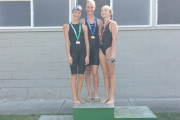 Neptunes swimmers, from left, Morgan Robertson-Weir, Jaylen Rushton and  Chloe Malenfant own the podium after sweeping 50 meter butterfly event. — Submitted photo