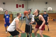 Tourney organizer, Jeremy Phelan prepares to toss up the ball between Adam Berg (left) and Tobin Eberle during the opening game of the 2016 Bomber Alumni Basketball Tournament Boxing Day at the Trafalgar Middle School Gymnasium. — The Nelson Daily photo