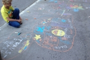 An aspiring young artist colours the sidewalk on 400 Baker Street during opening night of Artwalk. — The Nelson Daily photo