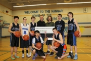 Tom Atkins of the Nelson and District Credit Union (fourth from left) presents Bomber coach Jeremy Phelan and the rest of the team with a cheque to help with costs at the Triple-A Boy's Basketball Championships in Langley. — The Nelson Daily photo