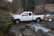 The silver Toyota Tacoma pickup sits in Cottonwood Creek while firefighters prepare to have the vehicle removed. — Submitted photo