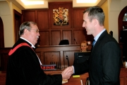 Provincial Court Judge Donald L. Sperry shakes hands with Nelson's newest member of the police department, Const. Christopher Duncan. — Photo courtesy Jaimie Killen