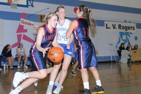 Angela Hamilton (7) of the Hawks gets help from a teammate to get past Devyn Parker of the Bombers during Saturday's Kootenay Girl's AA Hoop Final at the Hangar. — Bruce Fuhr photo