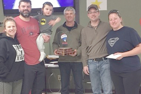 Remax Realty sponsor Glen Darough (center) presents the James MacKenzie with the top prize at the weekend Nelson Curling Club Valentines Mixed Bonspiel. From left, lead Michelle Kooznetsoff, second Brad Hildebrand, skip James MacKenzie and third Susan MacKenzie. — Submitted photo